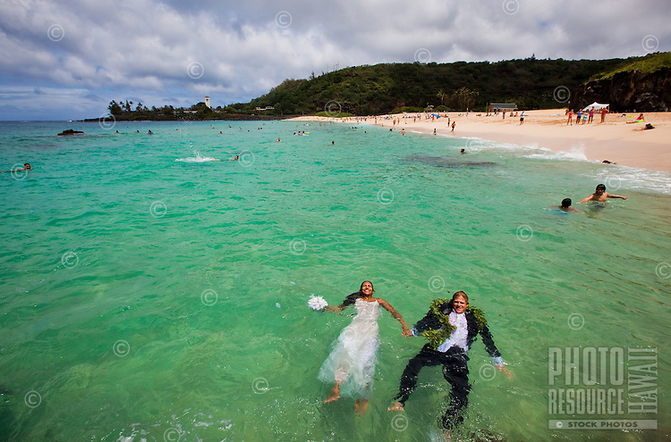 Couple enjoying the blue waters of Waimea Bay in their wedding attire