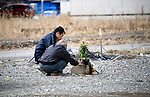 Kazunori Kawahara , 74 and another unidentified man lay flowers at the site of what was once Kawahara's sister's home  in Ofunato, Iwate Prefecture, Japan on 11 Mar 2012. .Photographer: Robert Gilhooly