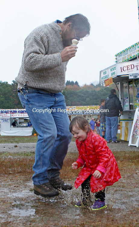 Harwinton, CT-100414MK13 John Coleman and his niece Dahlia louise enjoy splashing in a puddle at the 158th Annual Harwinton fair on Saturday.The inclement weather kept the crowds away, however, the gates will open at 8AM today with activities beginning at 9AM. Hay bale tossing, a new event, is scheduled to begin at 10AM. Michael Kabelka / Republican-American