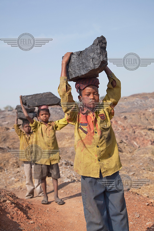 Boys carry large lumps of coal that they have scavenged from an open pit mine near Dhanbhad. They will carry this coal several kilometres to sell in a local market. As mining has displaced agriculture, scavenging for coal on the edge of mines has become one of the means of survival for those who have been displaced from an agricultural life by mining. .