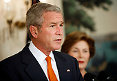 United States President George W. Bush announces he will widen economic sanctions on Myanmar's military rulers, piling on pressure for a transition to democracy after a bloody crackdown on anti-junta protests, in the Diplomatic Room of the White House in Washington, DC on October 19, 2007. The move comes only days after the European Union increased its sanctions against the regime. First lady Laura Bush looks on from right.<br /> Credit: Aude Guerrucci / Pool via CNP