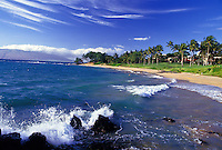 Maui's beautiful Wailea beach beneath a bright blue sky streaked with clouds.