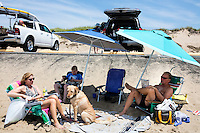 """Janice (from left), Reid (13), Tristan (13, near the car), and Scott Marble and their dog Daisy, sit near their car at Herring Cove Beach in the Cape Cod National Seashore outside of Provincetown, Mass., USA, on Fri., July 1, 2016. At right, pieces of eroded asphalt lay in the sand. Portions of the parking lot have been closed after land eroded during storms earlier this year. The Marble family spend their summers in Orleans, Mass., located on Cape Cod, and spend the rest of their year in Medfield, Mass. Scott, age 60, says he's been coming to the beach at least 40 years, and the couple have taken the boys to the beach since they were babies. """"We miss the whole length of it,"""" Janice said when asked about how the destroyed road and parking lot have changed the beach."""