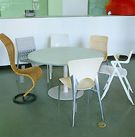 A collection of designer chairs, including an S chair by Tom Dixon, surround a circular table in the cafe of the Design Museum in Milan