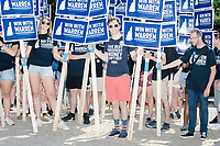 Supporters of Democratic presidential candidate and Massachusetts senator Elizabeth Warren hold campaign signs as they prepare to march in the 4th of July Parade in Amherst, New Hampshire, on Thu., July 4, 2019.