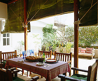 The balcony is adorned with green canvas blinds that can be rolled down to provide shelter from the hot sun and monsoon rains