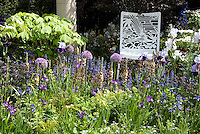Garden Chair with Bird Ornamentation Detal in Flower garden in spring