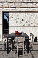 The shadow of the camouflage netting cast by the afternoon sun softens the exterior wall of the terrace