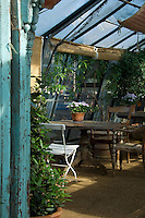 An old table and a random collection of chairs inside a greenhouse at Petersham Nursery