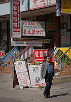 A man walks by various signs written mostly in Chinese are seen in Toronto Chinatown April 23, 2010. Toronto Chinatown is an ethnic enclave in Downtown Toronto with a high concentration of ethnic Chinese residents and businesses extending along Dundas Street West and Spadina Avenue.