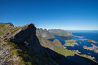 Female hiker stands on dramatic rock outcrop over village of Reine, Moskenesøy, Norway
