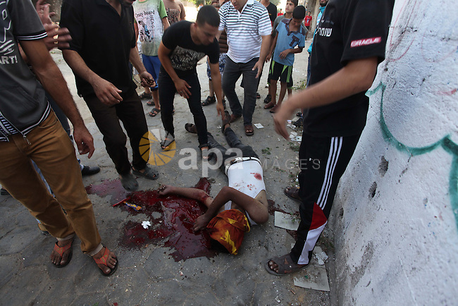 Palestinian paramedics move a victim of an Israeli air strike on a market place to an ambulance in the Shejaiya neighbourhood near Gaza City on July 30, 2014. At least 15 people were killed and 200 people wounded in an Israeli air strike on a market near Gaza City, medics said. The strike came shortly after the Israeli army said it was observing a humanitarian lull that would be in force for four hours from 1200 GMT. . Photo by Ashraf Amra