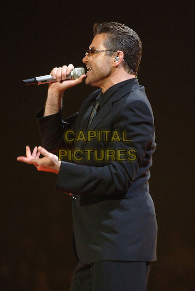 GEORGE MICHAEL.Perfoming at Earl's Court, London, UK..November 25th , 2006 .half length stage concert live gig performance music sunglasses shades black suit profile singing.CAP/BEL.©Belcher/Capital Pictures