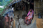 An enceinte woman sits on the entrance of her room at a camp for Rohingya people.