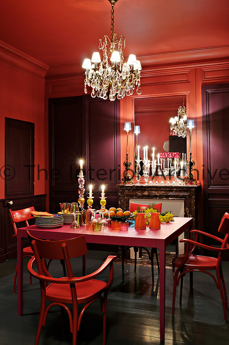 The dramatic red dining room is filled with candlelight in expectation of the evening meal
