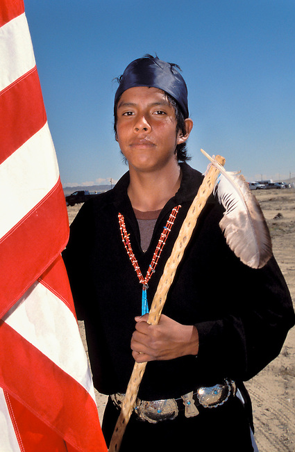 Navajo teenager, Austin Todechinii carrys a US flag along with a Navajo coup stick made from cactus wood