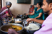 Archana's husband (right) fills tiffin containers, as she (center) makes bread in her house with her family in Anand, Gujarat, India on 11th December 2012. Archana , an ex-surrogate, continues to work with Dr. Nayana Patel, catering specially prepared tiffin meals to the surrogates and Akanksha IVF and Surrogacy clinic staff. Photo by Suzanne Lee / Marie-Claire France
