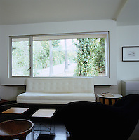 A modern white leather sofa in front of a large picture window
