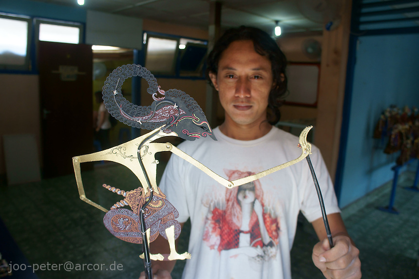 craftsman shows newly finnished wayang kulit (leather puppet) in a small manufactory, sultans palace, Yogyakarta, island Java, archipelago of Indonesia,  September 2011