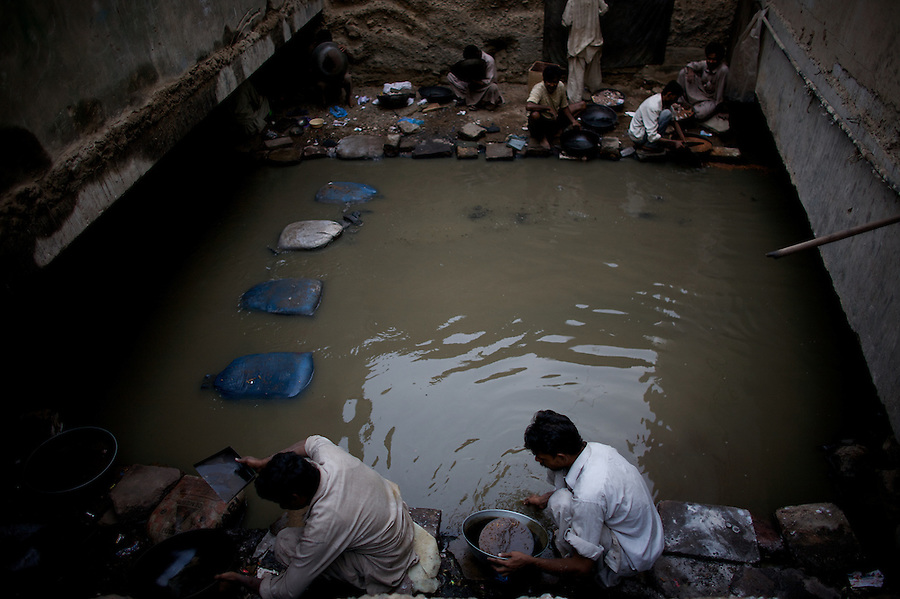 Men search for small particles of gold   in an open sewage  that have been  washed out from a nearby jewelry district in Karachi, Pakistan on Friday December 05 2008. The men say that they make very little money, just enough to buy a dose of heroin now and then.///..While Bangladesh, India, Nepal and Maldives all suffer from drug consumption, Pakistan is the worst victim of the drug trade in South Asia. Today, the country has the largest heroin consumer market in the south-west Asia region..The drug addicts resort to crime for generating income for the purchase of narcotics. The situation is becoming serious due to the number of heroin addicts in the country. An alarming rate of increase of 100,000 addicts per year is highly dangerous to society. The drug addicts are affecting nearly 20 million dependents and family members with psychological, social, and economic repercussions.