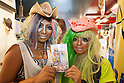 (L to R) Erimokkori of the Ganguro Cafe &amp; Bar with a female customer who has been transformed into a ganguro girl shows off a set of purikura pictures shot in a photo booth in the Shibuya shopping area on September 4, 2015. <br /> <br /> Ganguro is an alternative Japanese fashion trend which started in the mid-1990s where young women, rebelling against the traditional idea of Japanese beauty, wore colorful make-up and clothes and had dark-skin.<br /> <br /> 10 Ganguro fashion girls work in the new bar, which offers original Ganguro Balls (fried takoyaki style sausage balls in black squid ink batter) on its menu. Ganguro Caf&eacute; &amp; Bar also offers special services such as Ganguro make-up and the chance to take purikura (photo booth pictures) with staff and to look like a Ganguro girl walking around the Shibuya streets.<br /> <br /> The bar is popular with both Japanese and foreigners and has menus translated in English. (Photo by Rodrigo Reyes Marin/AFLO)