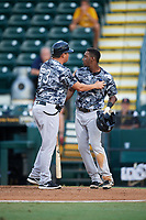 Tampa Yankees coach Raul Dominguez (left) holds Jorge Mateo (right) back from umpire Derek Thomas (not shown) after being ejected for drawing a line in the batters box with his bat during the second game of a doubleheader against the Bradenton Marauders on June 14, 2017 at LECOM Park in Bradenton, Florida.  Tampa defeated Bradenton 5-1.  (Mike Janes/Four Seam Images)