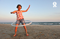 Girl playing with plastic hoop on beach at sunset (Licence this image exclusively with Getty: http://www.gettyimages.com/detail/92351854 )