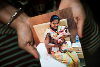 Sharda Solanki, 36, holds a photograph of a baby she carried during one of 2 of her surrogacies as she sits in her house in Anand, Gujarat, India on 9th December 2012. While her husband Kantibhai works as a security guard earning 5000 rupees per month, Sharda had made hundreds of thousands with 2 surrogacies that she did with Akanksha Clinic, which she used to buy land, buffaloes, build washrooms in her house and extend the house. She had also saved a substantial amount to fund her 3 children's educations and make sure that her 2 daughters will find husbands to match their current status. Photo by Suzanne Lee / Marie-Claire France