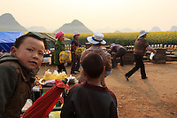 Luoping, Yunnan. Le chemin qui même aux collines est devenu un marché à ciel ouvert. Apiculteurs et marchands reçoivent les touristes.///Luoping, Yunnan. The road that leads to the hills has become an open-air market. Beekeepers and other vendors await the tourists.