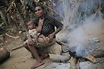 A Baka woman are cooking while nursing her son, Cameroon.
