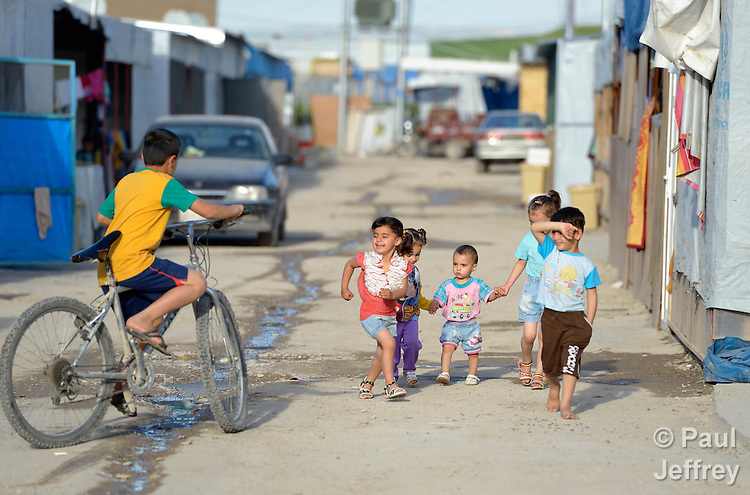 Children walk along the street in a camp for internally displaced families in Ankawa, near Erbil, Iraq, on April 8, 2016. Residents of the camp, mostly Christians, were displaced from Mosul, Qaraqosh and other communities in Iraq when ISIS swept through the area in 2014.