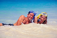 A couple wearing snorkel gear have fun on a white sand beach with beautiful turquoise water in the background.