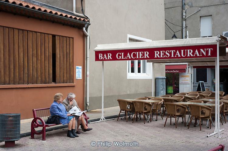 Two elderly women sitting on a bench in the street in Alès, France.