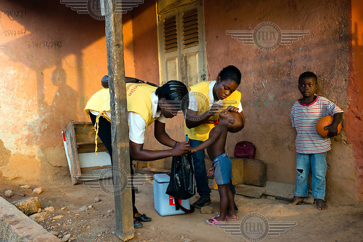 Bright Dzifa and Regina Baaka vaccinating a child during a National Immunisation Days (NID) polio eradication campaign.