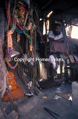 Hanuman Hindu deity Bombay India. An Hindu Holy man or Sadhu, stands on one leg resting on a swing. He is on the second penance ( in the second year) each penance is for 7 years, standing on one leg only. Local villagers help and provide for him. He is living under a Banyan tree. Remarkably he was reading English poetry transplated from a Russian book. He did talk a little too me, but the local people who gathered explained what he was doing.