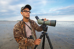 Birder looking for shorebirds on mudflats in South Korea. October.