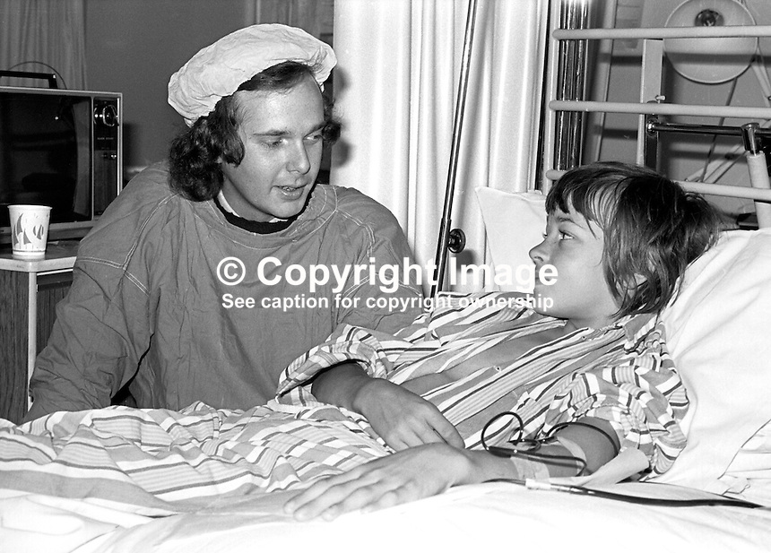 Lord Melchett, aka Peter Melchett, junior minister, N Ireland Office, visits a young patient in the kidney unit, Belfast City Hospital, September 1976. 197609000511<br />