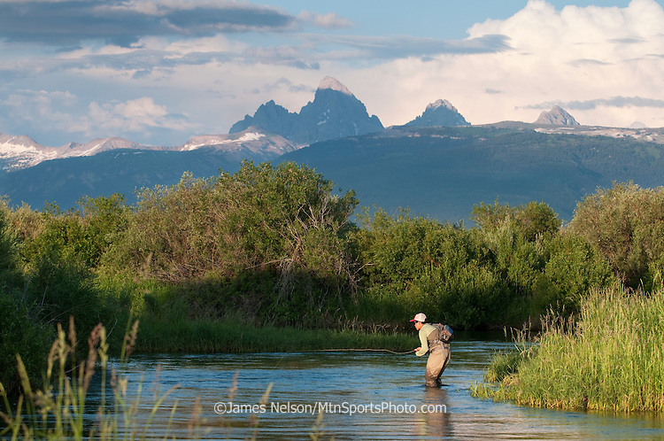 An angler fly fishes for trout during a summer evening on the Teton River near Driggs, Idaho.