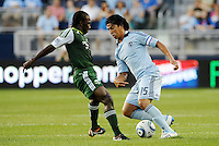 Roger Espinoza (15) midfielder Sporting KC moves past Diego Chara (21) midfielder Portland Timbers... Sporting Kansas City defeated Portland Timbers 3-1 at LIVESTRONG Sporting Park, Kansas City, Kansas.