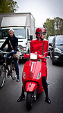 FRANCE, Paris, A young woman wearing all red on a red scooter in traffic. Another woman wearing blue in the background