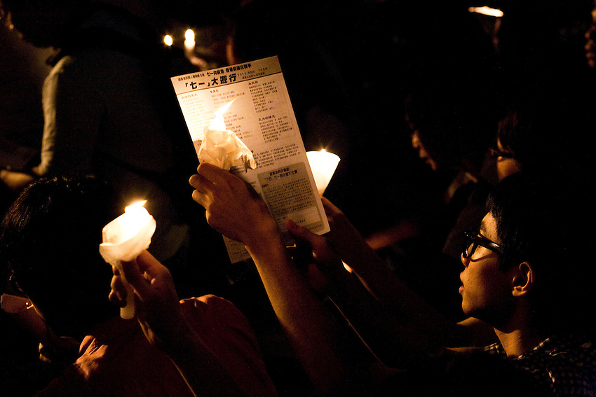 A young hongkonger is reading political tract with the light of his candle during the vigil for the anniversary of the Tiananmen June 4th crackdown. Youths are more and more implicated in political movement as the conflit about universal suffrage raisees in the Island. Hong Kong, june 4 2010.