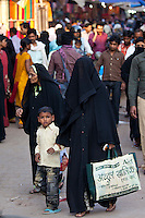 Street scene in holy city of Varanasi, muslim woman in black veil burkha shopping with her child, India