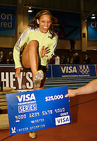 Lolo shows that winning hurdling for over her VISA CHAMPIONSHIP SERIES $25,000 check. Photo by Errol Anderson, The Sporting Image.