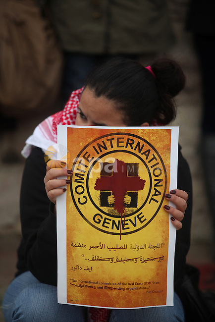 """Palestinian protesters hold posters and a sign reading """"ICRC, do your work or leave"""" during a demonstration in support of Palestinian prisoners held in Israeli jails, some of whom are observing a hunger strike, outside the Red Cross office in Al-Bireh, a town adjacent to the West Bank city of Ramallah, on December 20, 2012. Protesters called on the Red Cross to intervene more in order to make conditions better for the prisoners. Photo by Issam Rimawi"""