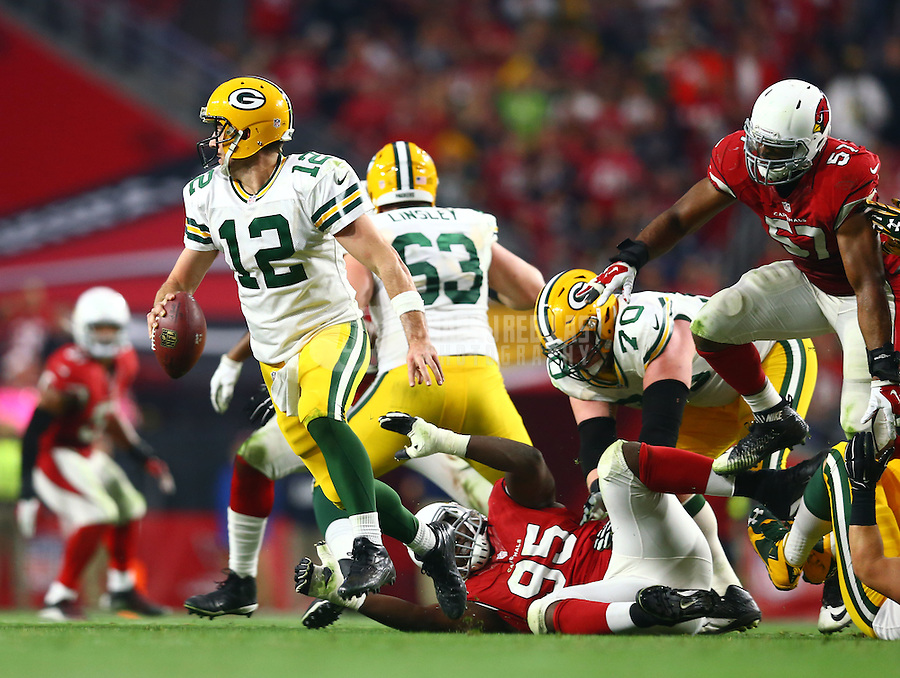 Dec 27, 2015; Glendale, AZ, USA; Green Bay Packers quarterback Aaron Rodgers scrambles in the second half as he avoids the tackle of Arizona Cardinals defensive end Rodney Gunter (95) at University of Phoenix Stadium. The Cardinals defeated the Packers 38-8. Mandatory Credit: Mark J. Rebilas-USA TODAY Sports