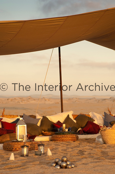 Numerous cushions, lanterns and candles create a comfortable and atmospheric seating area under this awning on the beach