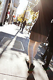 USA, California, San Francisco, a young woman walks down the sidewalk into the sun on Valencia Street