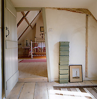 View from the landing through the open door into the attic bedroom furnished with a wrought-iron bed