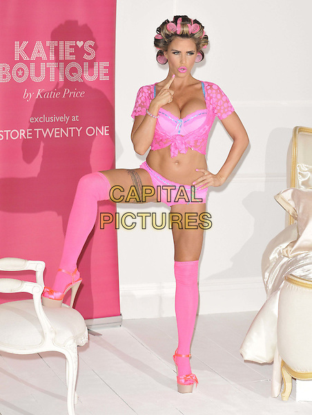Katie Price (Jordan).The launch photocall for Katie Price's new summer lingerie range for Store 21, The Worx, London, England..May 29th, 2012.full length pink lace top knotted bra cleavage belly stomach midriff knickers underwear tattoo tights stockings garter beige platform sandals shoes rollers curlers in hair hand on hip hair leg up chair finger mouth open  .CAP/CAN.©Can Nguyen/Capital Pictures.