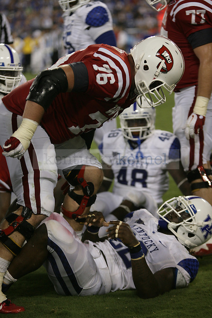 WKU right guard Adam Smith looks down at the fallen UK defender during the second half of UK's season opener against Western Kentucky at LP Field in Nashville, Tennessee. Monday, Sept. 1, 2011 in Lexington, Ky.  Photo by Brandon Goodwin   Staff